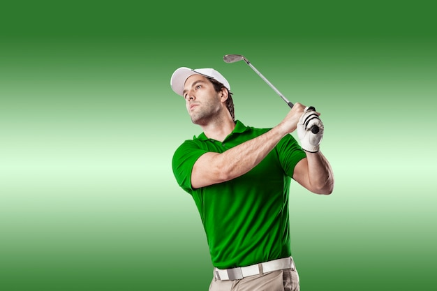 Golf player in a green shirt taking a swing, on a green background.