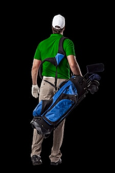 Golf player in a green shirt walking with a bag of golf clubs on his back, on a black background.