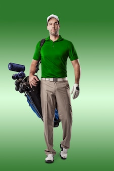 Golf player in a green shirt walking with a bag of golf clubs on his back, on a green background.