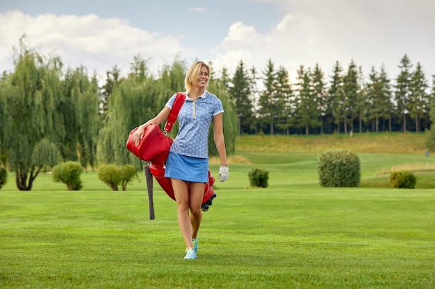 Golf player holding golf equipment on green field