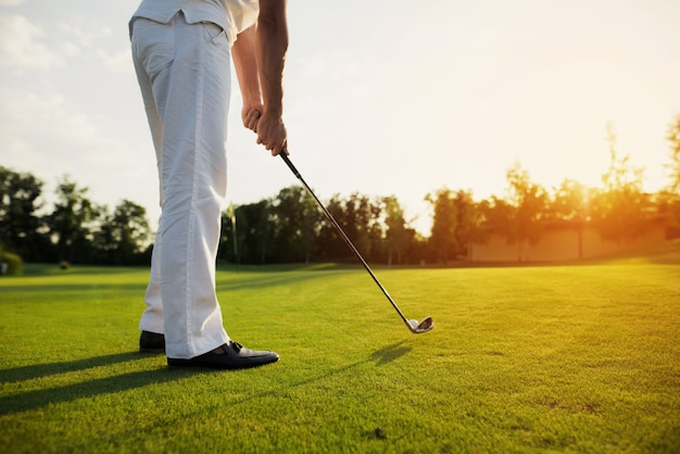 Golf player holds golf club going to take shot.