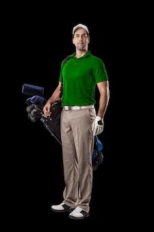녹색 셔츠에 골프 선수, 검은 배경에 그의 뒤쪽에 골프 클럽의 가방과 함께 서.