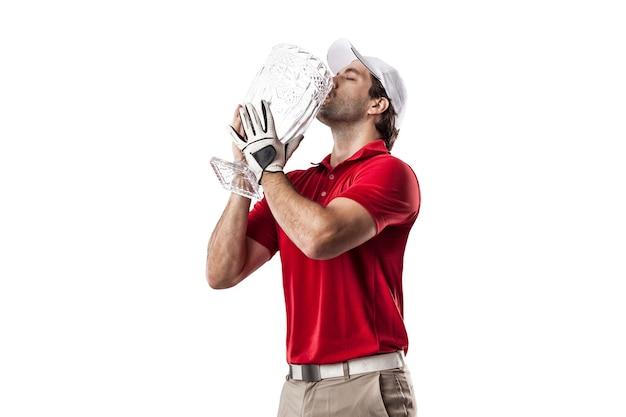 Игрок в гольф в красной рубашке празднует со стеклянным трофеем в руках, на белом пространстве.