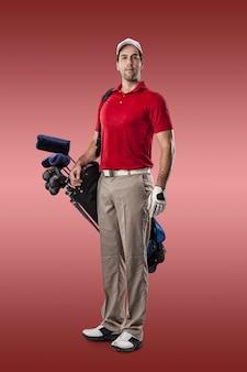 빨간색 배경에 그의 뒤쪽에 골프 클럽의 가방과 함께 서있는 빨간색 셔츠에 골프 선수.
