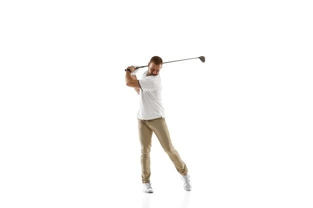 コピースペースで白い壁に分離されたスイングを取っている白いシャツを着たゴルフプレーヤー。明るい感情と表情で練習するプロ選手。スポーツコンセプト。