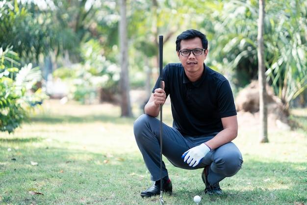 コースティーでゴルフをするためにフィールドを見て座っているゴルフプレーヤー