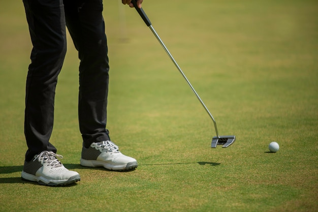 Golf player at the putting green hitting ball into a hole