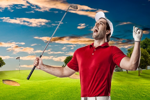 Golf player in a red shirt celebrating, on a golf course.