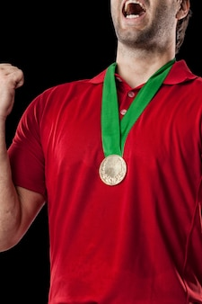 Golf player in a red shirt celebrating with a golden medal, on a black background.