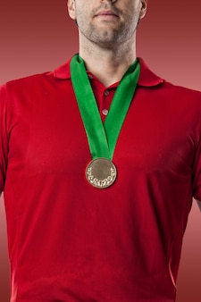 Golf player in a red shirt celebrating with a golden medal, on a red background.