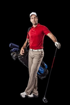 Golf player in a red shirt, standing with a bag of golf clubs on his back, on a black background.