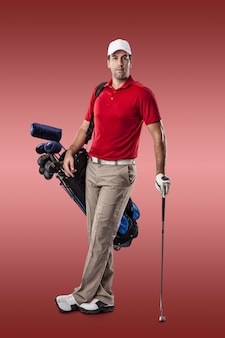 Golf player in a red shirt, standing with a bag of golf clubs on his back, on a red background.