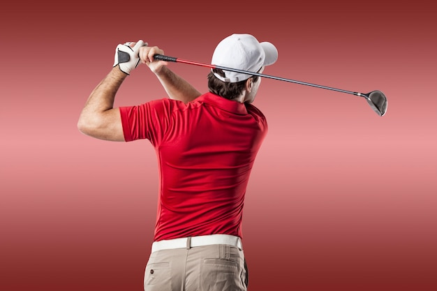 Golf player in a red shirt taking a swing, on a red background.