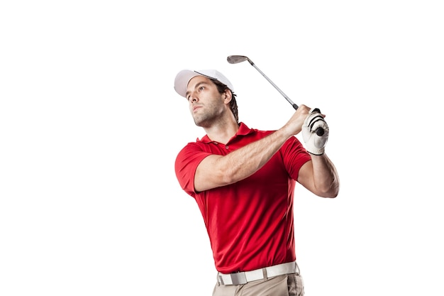 Golf player in a red shirt taking a swing, on a white space.