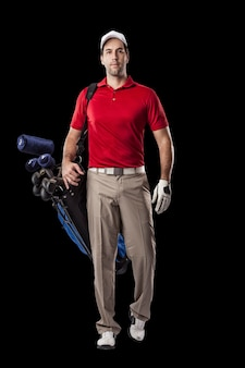 Golf player in a red shirt walking with a bag of golf clubs on his back, on a black background.