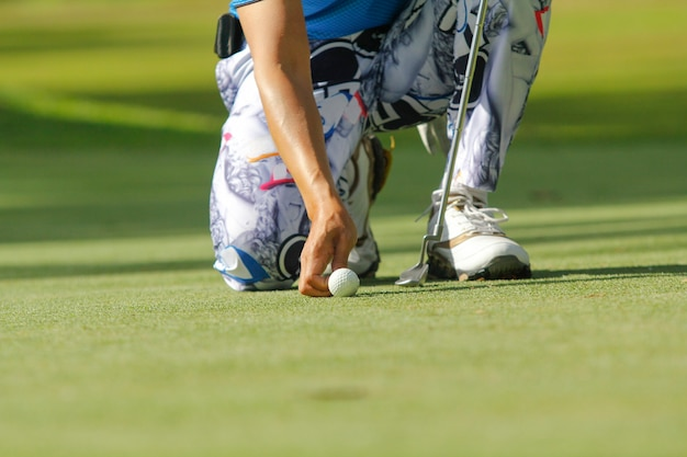 Игрок в гольф на корточках, чтобы положить мяч