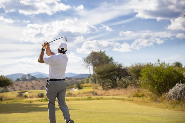 Golf player swing on cloudy sky