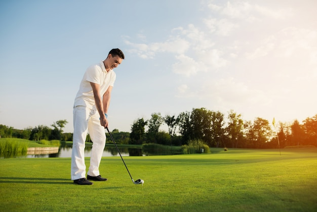 Golf player taking shot ball is on the tee.
