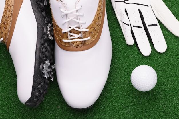 골프 신발 공과 흰색 장갑 녹색 잔디에 누워