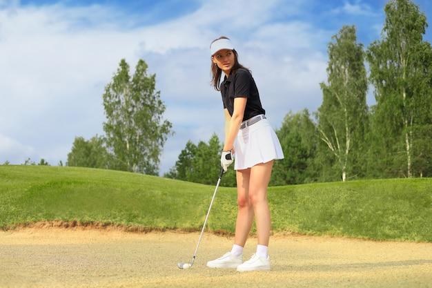 Выстрел в гольф из песчаного бункера игрок в гольф ударяет по мячу от опасности.