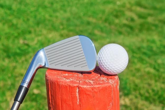 Golf stick upside down on a wooden ball pedestal on the grass. close-up.