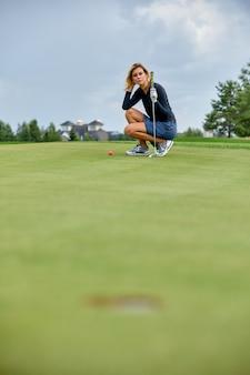 Golfer action, чтобы выиграть после долгой игры в гольф на зеленом поле. девушка играет в гольф. гольф концепция, лунка