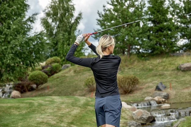 Golfer action to win after a long game of golf on a green field. the girl is playing golf. golf concept, outdoor sports.