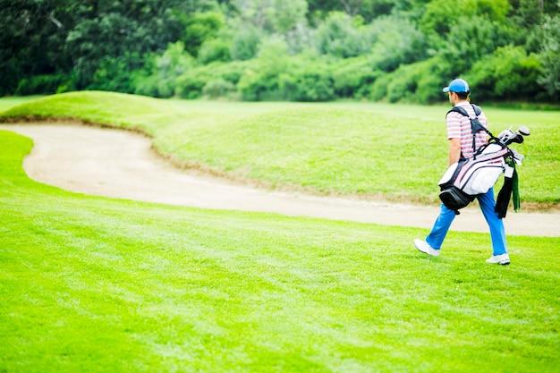美しい晴れた日に彼の機器を運ぶゴルファー