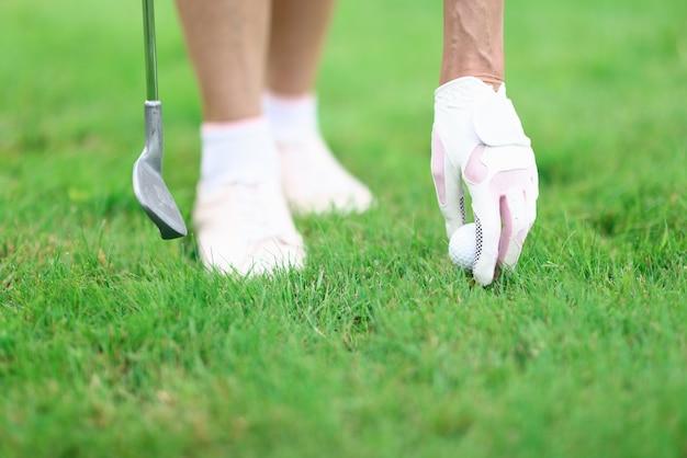골퍼는 골프 공을 고치고 골프 클럽을 손에 쥐고 있습니다.