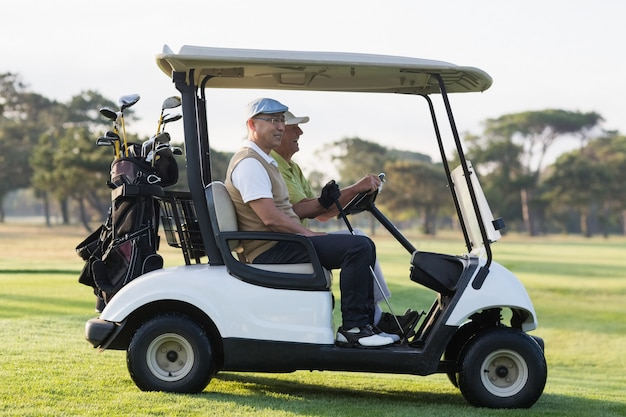 Golfer friends sitting in golf buggy