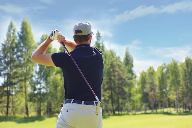 ゴルファーがクラブハウスに向かってフェアウェイショットを打つ。