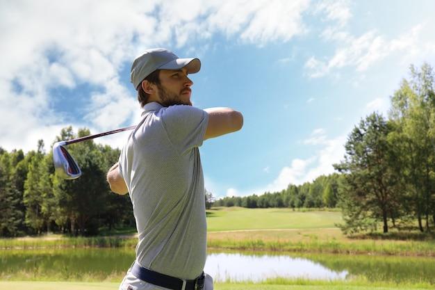 Игрок в гольф бросает удар клюшкой на поле во время летних каникул.