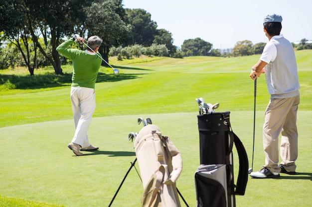 Golfer holding hole flag for friend putting ball Premium Photo