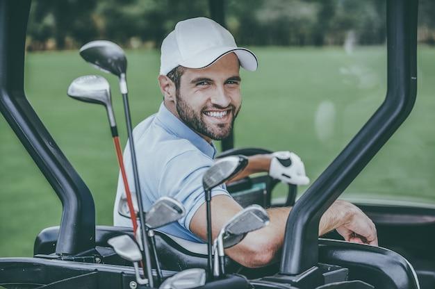 Игрок в гольф в тележке для гольфа. вид сзади молодого счастливого мужчины-гольфиста, управляющего тележкой для гольфа и смотрящего через плечо