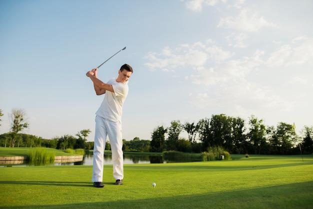 Golfer is taking swing shot on course neat lake.