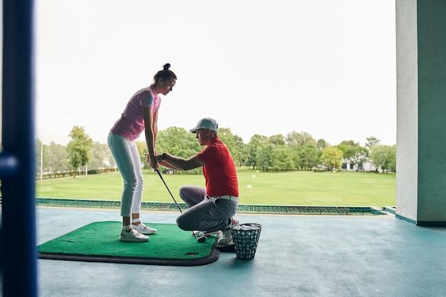 코치의 도움을 받아 아이언 클럽을 잡는 방법을 배우는 골퍼