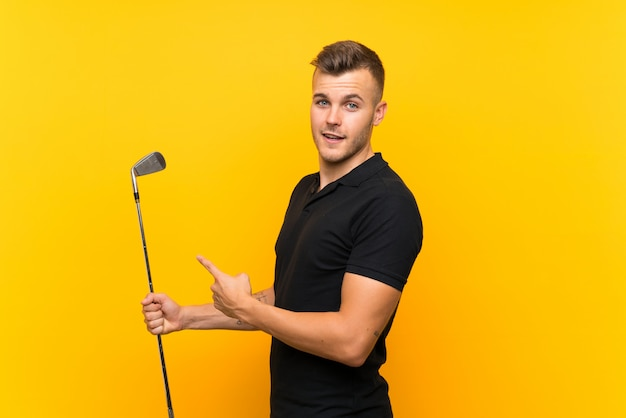 Golfer player man over isolated yellow background and pointing it