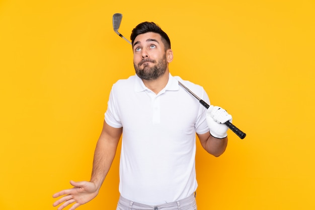 Golfer player man over isolated yellow wall making doubts gesture while lifting the shoulders