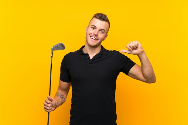 Golfer player man over isolated yellow wall proud and self-satisfied