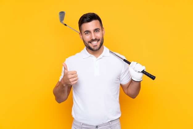 Golfer player man over isolated yellow wall with thumbs up because something good has happened