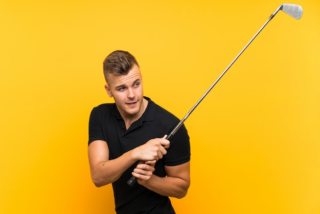 Golfer player man over isolated yellow wall