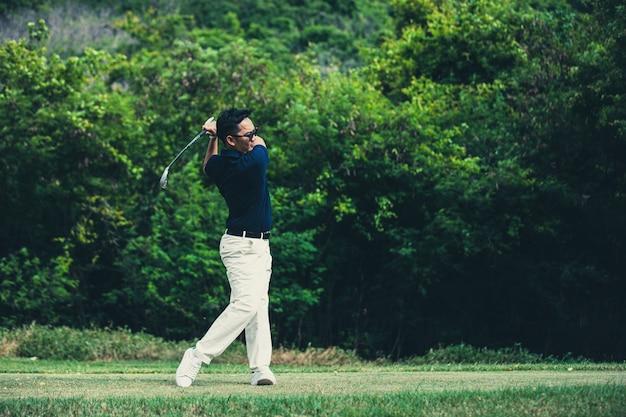 Гольфист играет в гольф на поле для гольфа