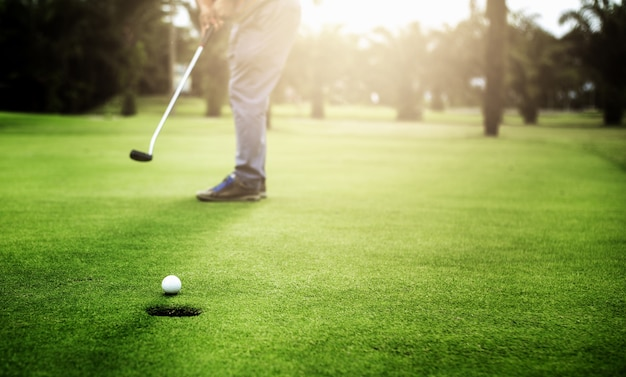 Игрок в гольф, играющий в мяч для гольфа, подходит к гольф-лунке на зеленом поле для гольфа