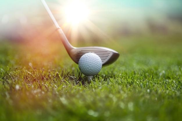 Golfer putting golf ball on the green golf, lens flare on sun set evening time.