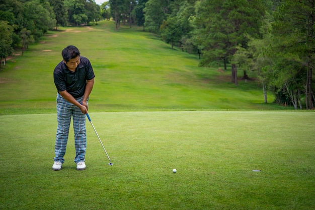 緑のコースの穴にゴルフボールを置くゴルファー