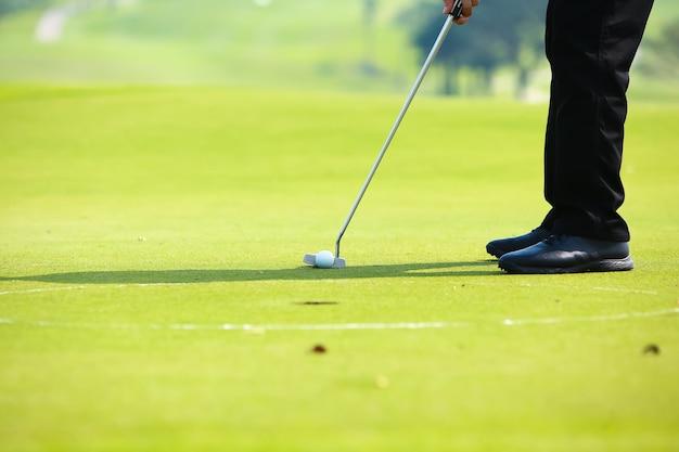 Гольфист положить мяч для гольфа на зеленом поле для гольфа