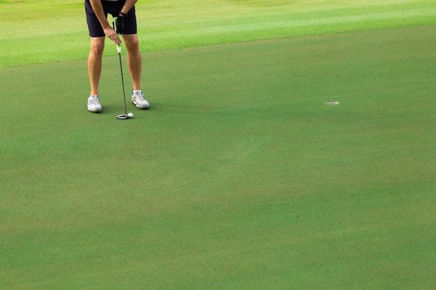 Гольфист ставит мяч для гольфа на зеленый гольф,
