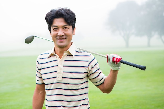 Golfer standing and holding his club smiling at camera