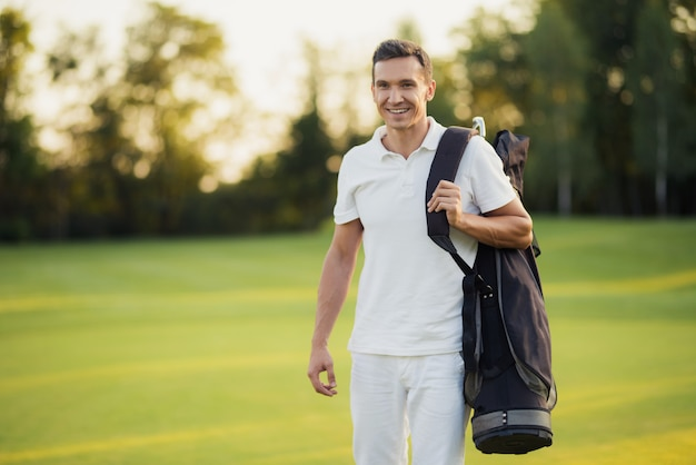 Golfer with bag of clubs leaves a gulf course.