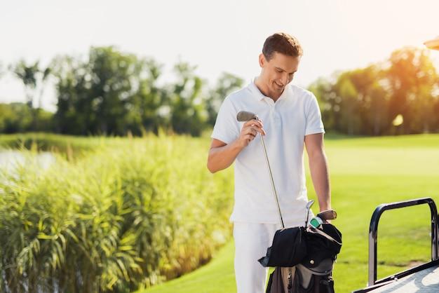 Golfer with golf sticks golf bat set at buggy car.